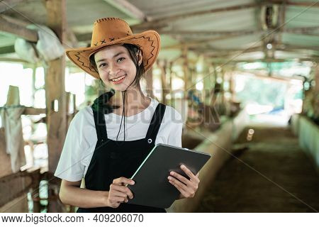 Close Up Of A Smiling Woman Wearing A Cowboy Hat Carrying A Digital Tablet