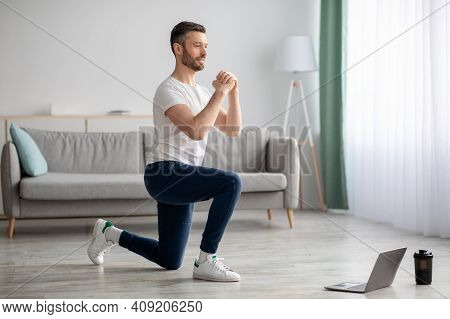 Positive Athletic Bearded Middle-aged Man Doing Exercises At Home, Using Laptop, Watching Sport Vide