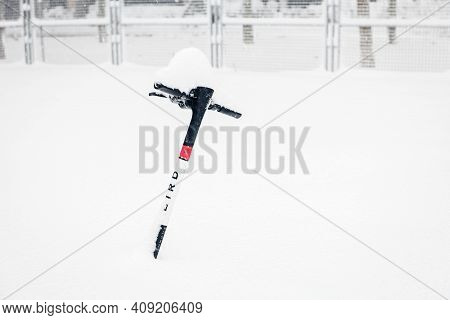 Madrid - January 9, 2021: A Modern Electric Scooter Stranded Under The Snow During The Heavy Filomen