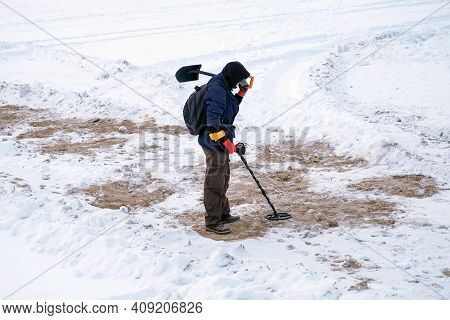 Treasure Hunter Is Looking For Treasures On The Winter Snow With A Metal Detector.