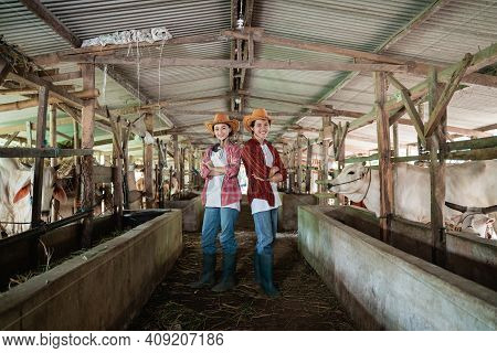 Two Cattle Breeders Wearing Casual Clothes And Hats Stand Back To Back And Pose Crossed Hands