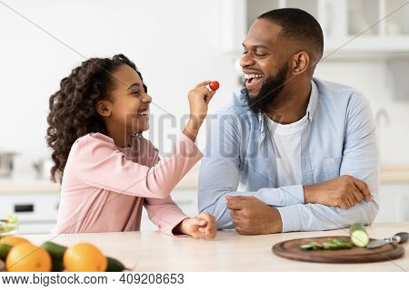 Healthy Meal. Cute African American Kid Girl Feeding Her Happy Father With Tomato While They Cooking