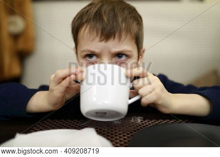 Portrait Of Child Has Tea In Restaurant