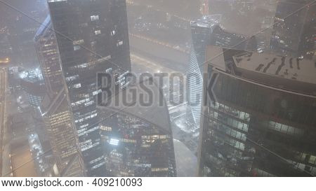 Glowing Skyscrapers At Night In Winter. Action. Top View Of Beautiful Glowing Skyscrapers On Backgro