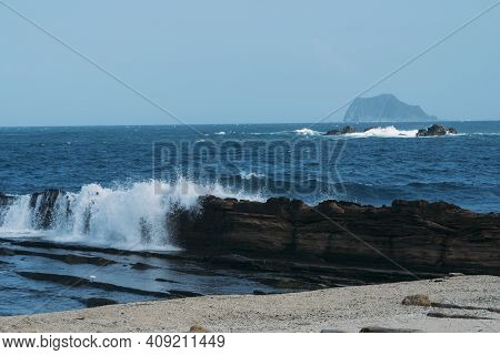 Wave Of Ocean Water Crashing Against Rocky Cliff With Blue Sea Behind In Yehliu, Taiwan.
