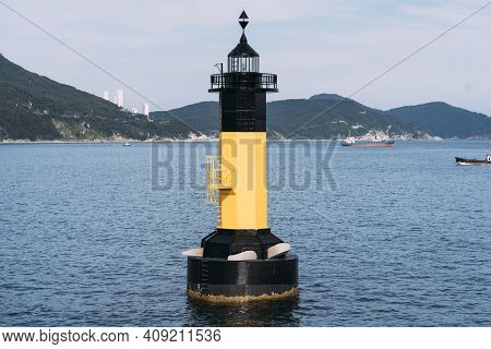 Landscape View Of Large, Yellow And Black Painted Lighthouse, Floating In The Sea In Busan, South Ko