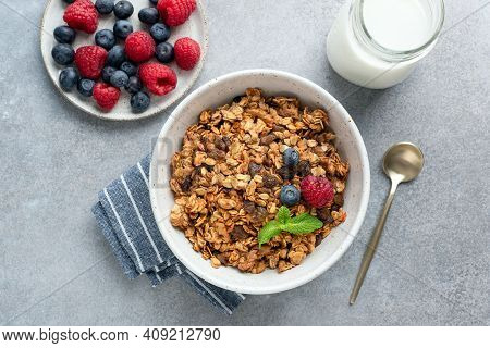 Granola Bowl With Raisins, Nuts And Fresh Berries. Homemade Crunchy Granola On Grey Concrete Backgro