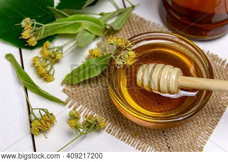 Stick For Honey In Glass Bowl With Linden Honey And Fresh Linden Flowers On A Wooden Table. Selectiv