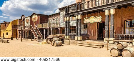 Vintage Far West Town With Saloon. Old Wooden Architecture In Wild West With Blue Sky Background.