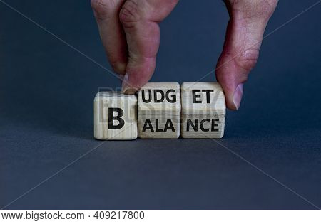 Budget Or Balance Symbol. Businessman Turns Wooden Cubes And Changes The Word 'balance' To 'budget'.