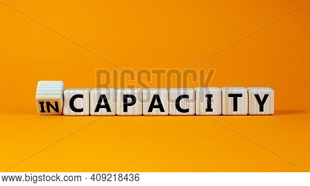 Capacity Or Incapacity Symbol. Turned A Wooden Cube And Changed The Word 'incapacity' To 'capacity'.
