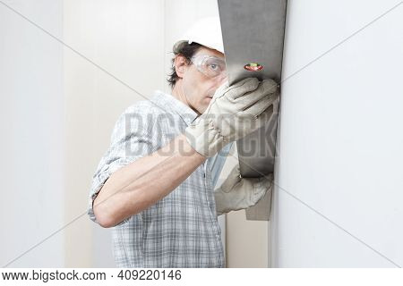 Man Drywall Worker Or Plasterer Checking Level Of White Plasterboard Wall With Bubble Level At Const