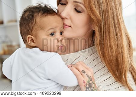 Loving Young Caucasian Mother Hugging Cute Infant African American Baby Daughter Expressing Single P