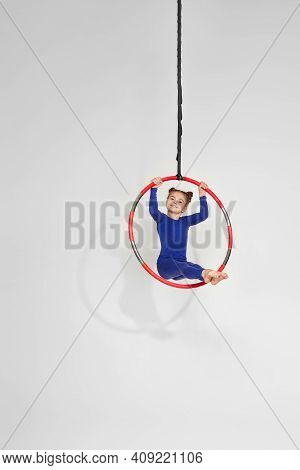 Beautiful Child Girl Gymnast Shows An Acrobatic Performance On An Aerial Hoop