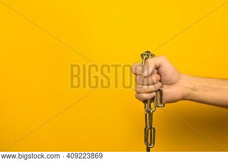 Male Hand Holding A Metal Chain On A Yellow Background Indoors. Copy Space.