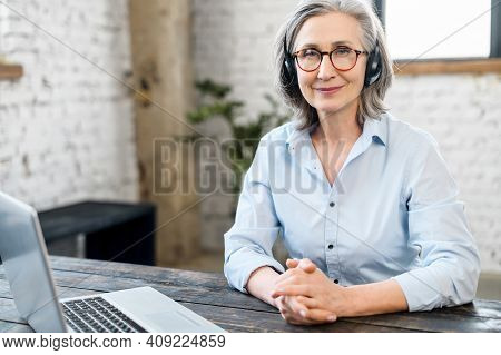 Mature Senior Office Worker Businesswoman With A Pleasant Smile In Headset And Glasses Looking At Th