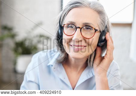 Headshot Portrait Of A Charming Smiling Elegant Senior Lady, Wearing Headset, Glasses Looking At The
