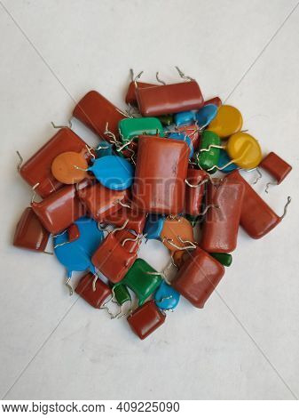 Multi Colored Bipolar Ceramic Capacitors Dismantled From Boards On A White Background