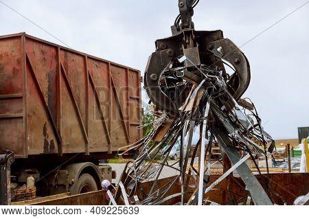 Loading Scrap Metal Into A Truck Crane Grabber Loading Metal Rusty Scrap In The Dock A Grapple Truck