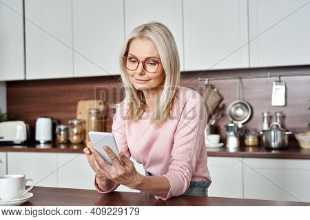 Middle Aged 50 Years Old Woman Using Apps Ordering Buying Food On Smartphone Sitting In Kitchen At H