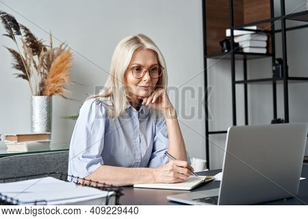 Middle Aged Older Business Woman Watching Professional Training Class, Online Webinar On Laptop Comp