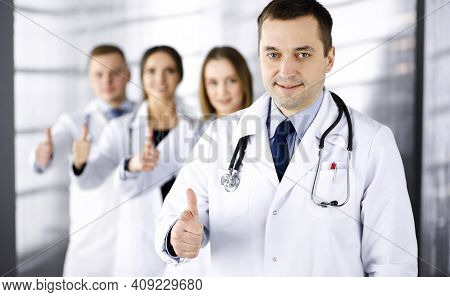 Group Of Professional Doctors Are Standing As A Team With Thumbs Up In A Hospital Office, Ready To H