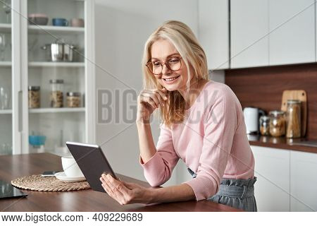 Happy Middle Aged 50 Years Old Woman Using Digital Tablet Sitting In Kitchen At Home. Mature Older L
