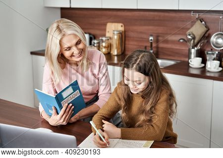 Happy Teen Child Daughter And Mom Learning English Together Studying At Home In Kitchen. Teenage Sch