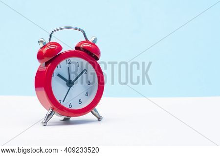 Red Round Analog Alarm Clock Isolated On Blue Background. Time 10:10.