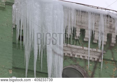 Big, Sharp Icicles And Melted Snow Hanging From Eaves Of Roof. Dangerous Icicles On The Roof. Danger