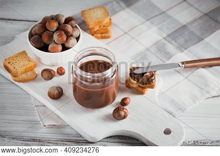 Little Toasts With Sweet Hazelnut Chocolate Spread For Breakfast On White Wooden Background