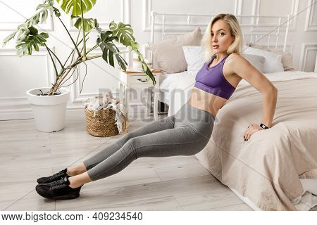 Sportive Blonde Girl In Gray Sportswear, Goes In For Sports, Does Back Push-ups From The Bed, Plank