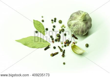 Whole Garlic And Garlic Cloves With Pepper With Bay Leaf And Cloves On A White Plate