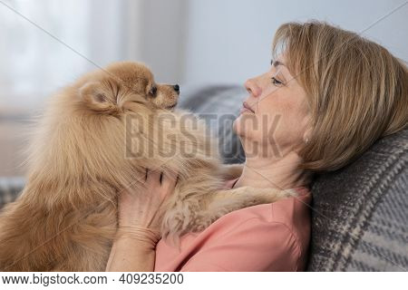 Happy Beautiful Positive Lady, Elderly Senior Woman Sitting At Couch In Living Room At Home With Her