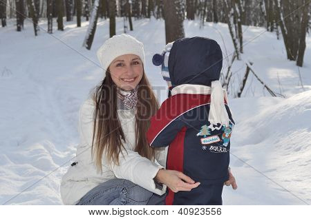 Young Smiling Mother Cares For The Baby On A Winter Walk