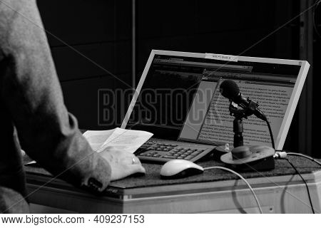 Bonn, Germany - April 9, 2018 : A Journalist Presenting News Live On Camera Behind His Computer