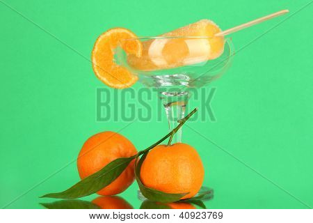 Yellow fruit juice ice in vase on green background