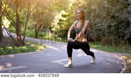 Woman Runner Stretching Legs Before Exercising Summer Park Morning Middle Age Athletic Female Warmin