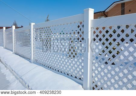 White Plastic Fence In A Modern Cottage Village On A Clear Winter Day. Snow Drifts In Front Of A Vin
