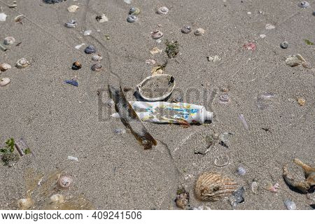 Used Tooothpaste Tube Discarded On Shells Beach Ecosystem, Sea Coast Pollution Contamination