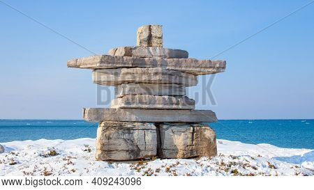 A Giant Inukshuk Stands Overlooking Georgian Bay At Collingwood's Sunset Point Park. A Monument In T