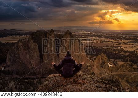 Adventurous Man Sitting In A Meditation Position On Top Of A Cliff. Dramatic Sunset Art Render. Take