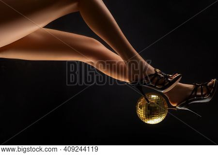 Disco Ball On High Heels. Party Legs. Disco Event. Woman Heels With Gold Disco Ball. Celebrate Conce