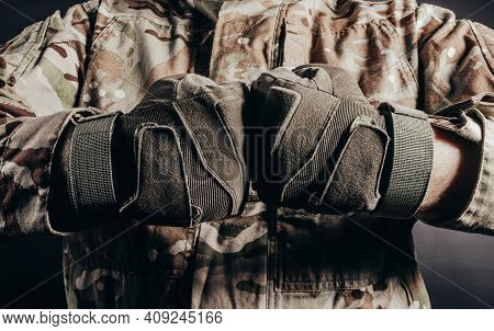 Photo Of Soldier In Camouflaged Uniform Showing Fist Fight Gesture In Tactical Gloves On Black Backg