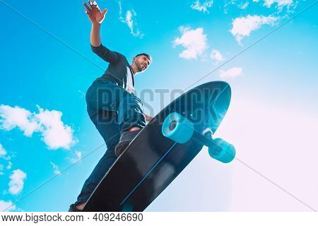 Skateboarder In Action. Man Riding On A Skateboard Outdoors On Sunny Summer Day. Blue Sky Background
