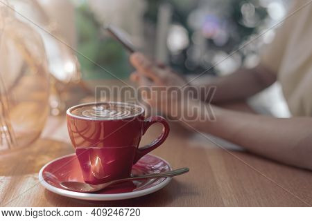 Close Up Hot Cappuccino, Latte Coffee With Blur Hands Of Woman Holding Mobile, Smart Phone Sitting I