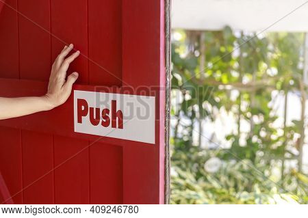 Hand Of Women Push And Hold Red Wood Door To Outdoor Park. Women Hand Hold Red Wood Door Have Push L