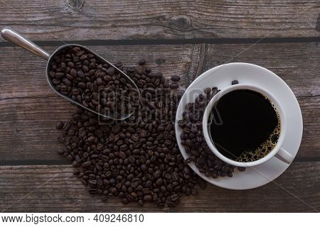 Top View Cup Of Coffee And Coffee Beans In A Sack On Wood Background. Close Up Hot Black Espresso Co