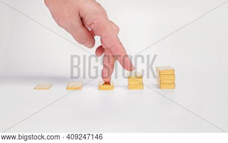 Women's Fingers Climb The Ladder Of Gold Bars. Gold Ingot On A Light Background