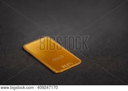 Gold Bar On A Black Background. Ingot On A Dark Surface